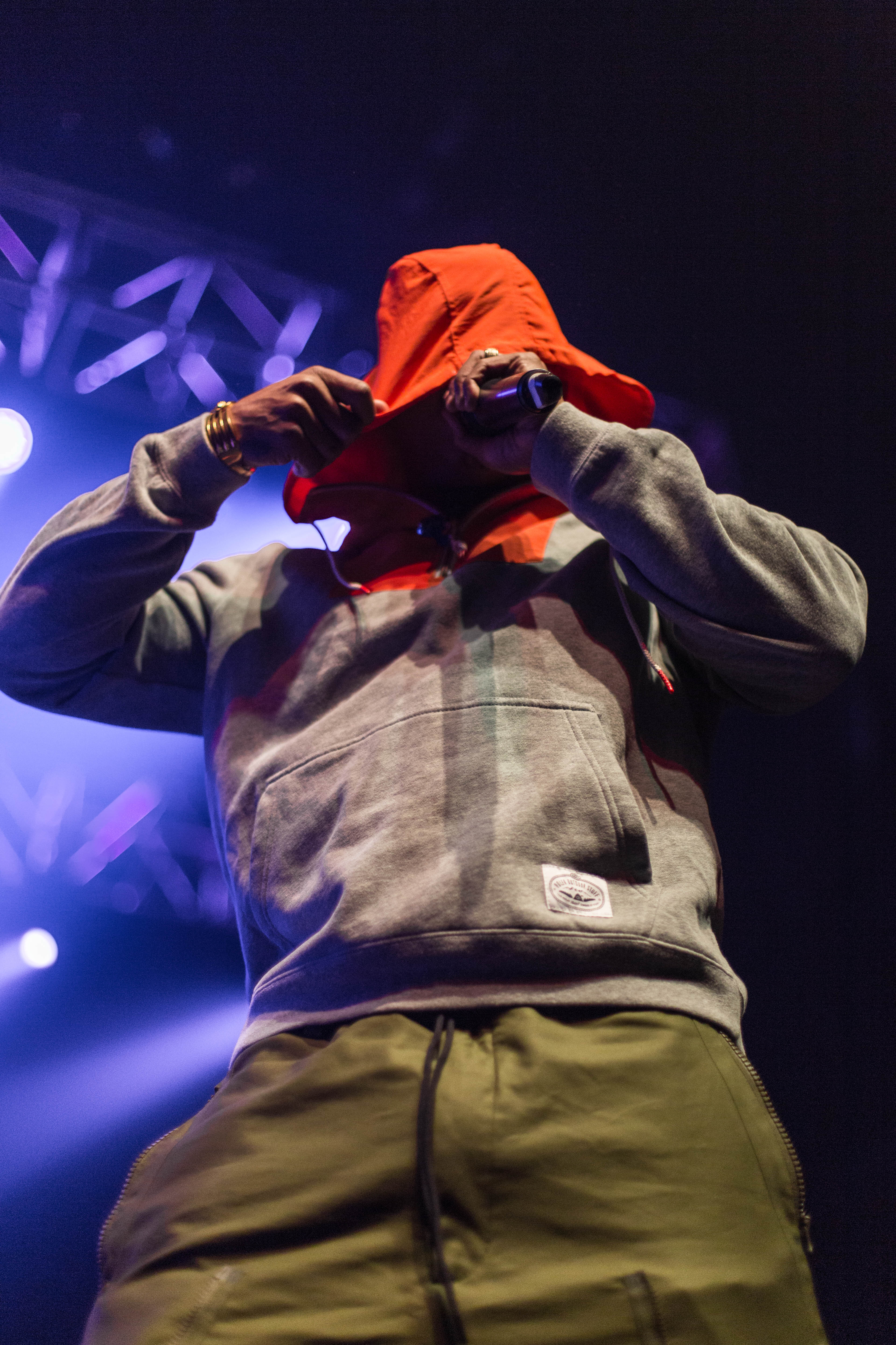 Ja Rule performing on stage with his hood over his head.